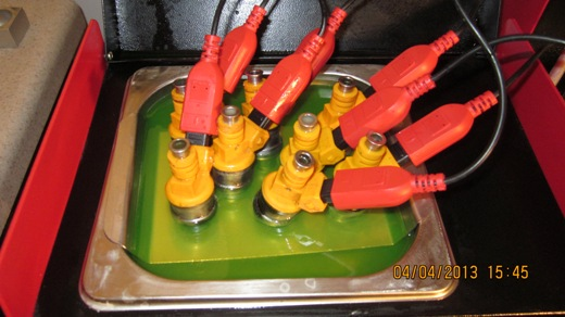 The fuel injectors are being cleaned in the ultrasonic cleaning tank while they are also being electronically cycled on and off by the computerized injector drive unit.